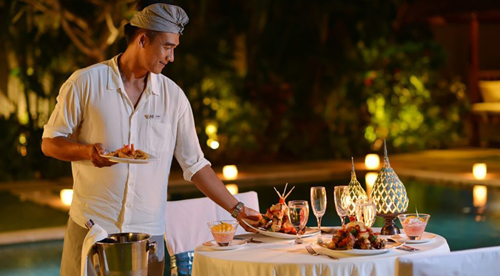 Staff-nyaman-villas-preparing-candle-light-dinner-by-the-pool-bali