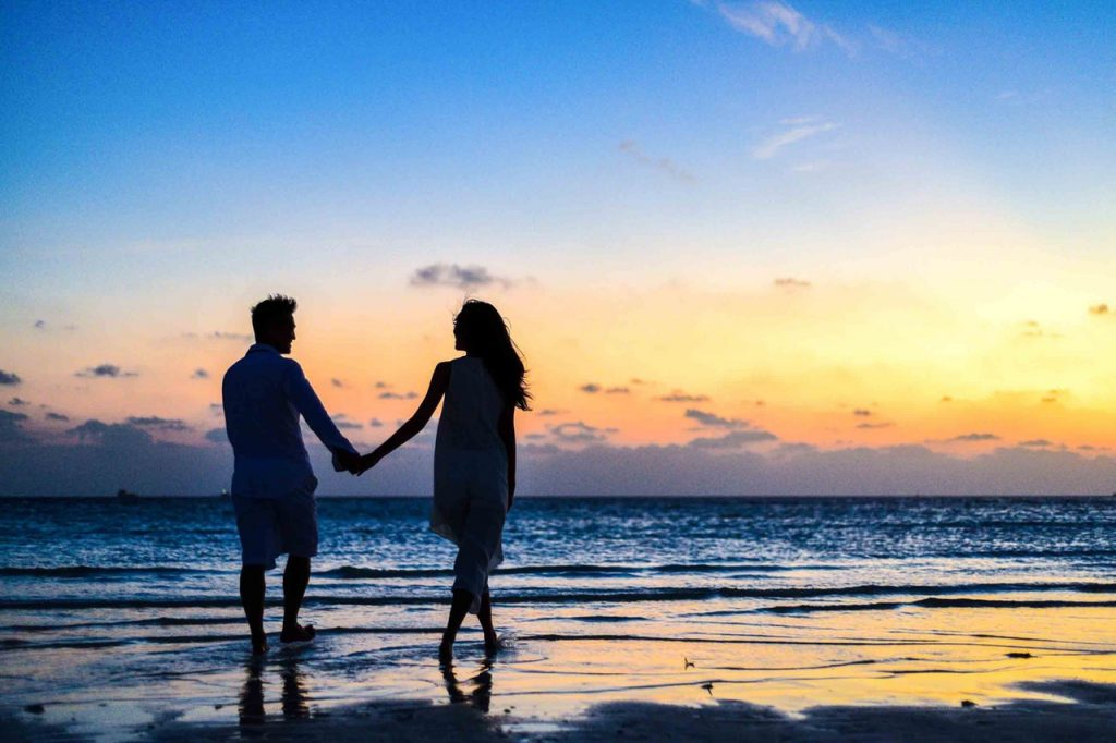 a-couple-walking-on-the-beach-during-sunset
