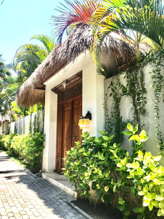 nyaman-villas-bali-image-villa-entrance-area-with wooden-doors-and-green-plants